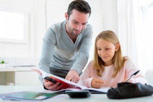 View of a Father helping out her daughter for homework