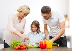 vegetarian food, culinary, happiness and people concept - happy family cooking vegetable salad for dinner over kitchen background