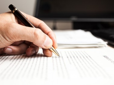 Close-up of a person writing on a document