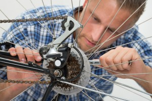 Close-up Of Young Man Repairing Bicycle With Spanner